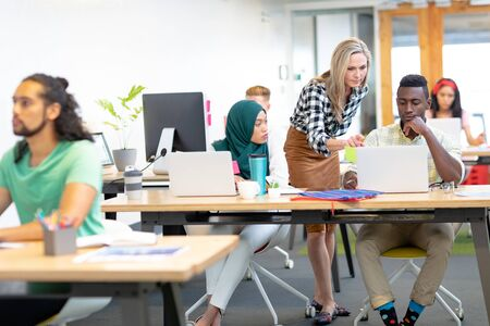 Front view of diverse business people discussing over laptop at desk in a modern office