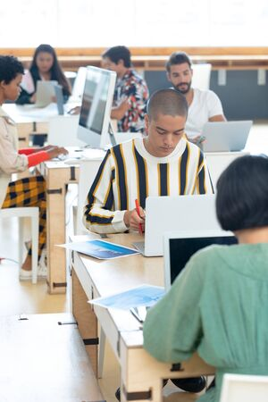 Front view of young Mixed-race Businessman working on desk in the modern office while colleagues working around him Stock Photo