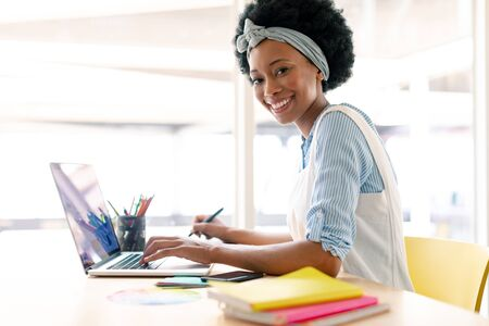 Side view of African american female graphic designer using graphic tablet and laptop at desk in office Stock Photo
