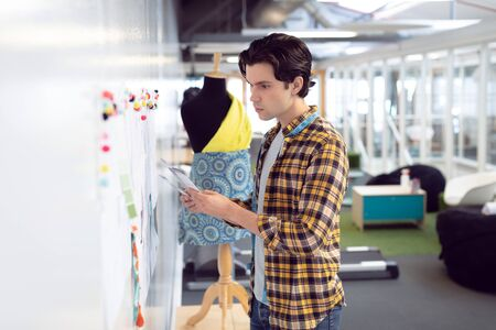 Side view of Caucasian male fashion designer looking at sketch in office Stock Photo - 124672519