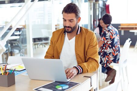 Front view of concentrated Caucasian businessman using laptop on desk in the modern office while colleagues speaking behind him