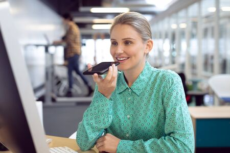 Front view of Caucasian female graphic designer talking on mobile phone at desk in office