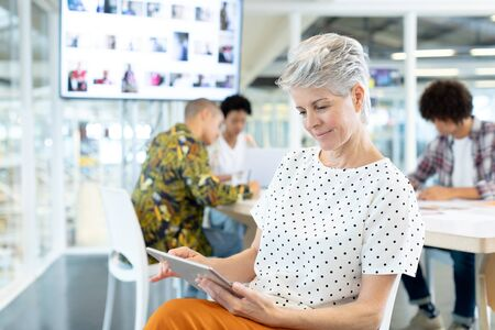 Front view of Caucasian female fashion designer using digital tablet while diverse business people discussing in the conference room at office