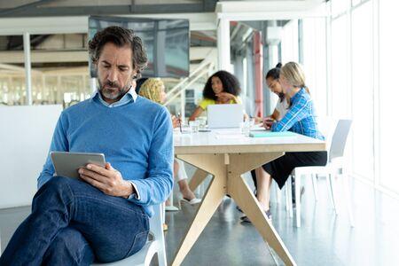 Vista frontal del empresario caucásico maduro trabajando en tableta digital en la sala de conferencias en una oficina moderna
