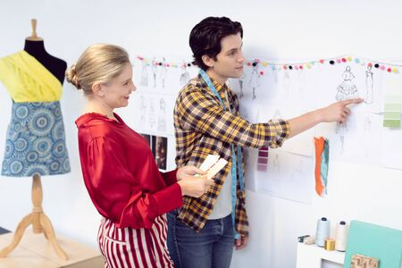 Side view of Caucasian male and female fashion designer discussing over sketch in office