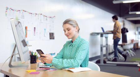 Front view of Caucasian female graphic designer using mobile phone at desk in office Stock Photo - 124672472