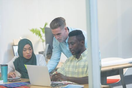 Front view of diverse business people working together on laptop at desk in a modern office