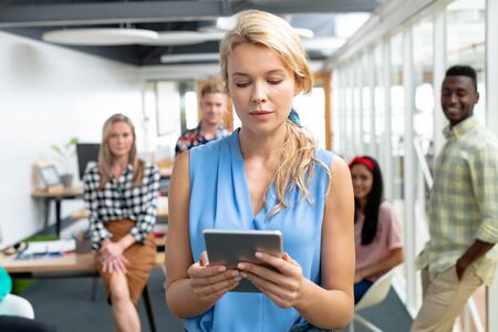 Front view of Caucasian businesswoman using digital tablet while diverse colleagues standing in background at office Imagens