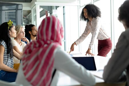 Vue de face de divers hommes d'affaires discutant entre eux dans une salle de conférence dans un bureau moderne