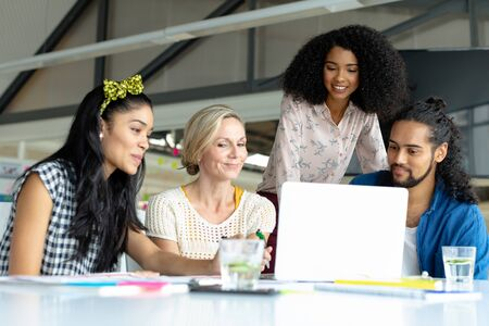 Front view of happy diverse business people working together on laptop at conference room in a modern office Stock Photo