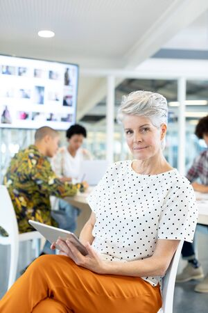 Portrait of Caucasian female fashion designer using digital tablet while diverse business people discussing in the conference room at office