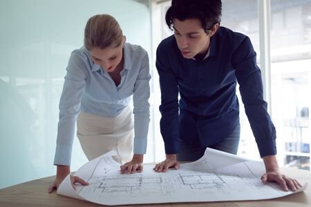 Front view of Caucasian male and female architects discussing over blueprint in office