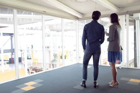 Rear view of Caucasian male and female architects interacting with each other in office