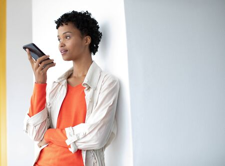 Side view of beautiful young African-american businesswoman talking on mobile phone in a modern office
