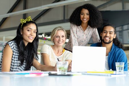 Front view of happy diverse business people looking at camera while working at conference room in a modern office Stock Photo