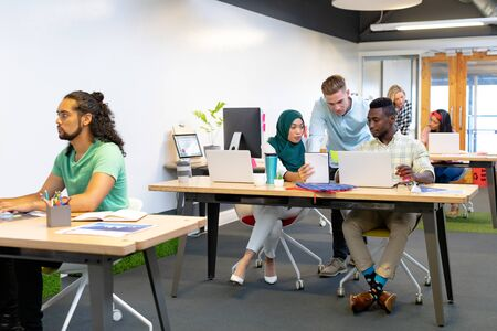 Front view of diverse business people working together at desk in a modern office