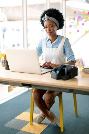 Front view of African american female graphic designer working on laptop at desk in office