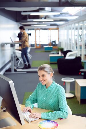 Side view of Caucasian female graphic designer working on computer at desk in office Stock Photo - 124672205