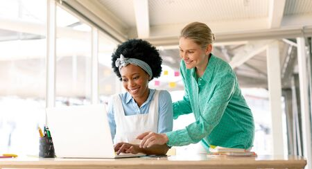 Front view of diverse businesswomen discussing over laptop at desk in office