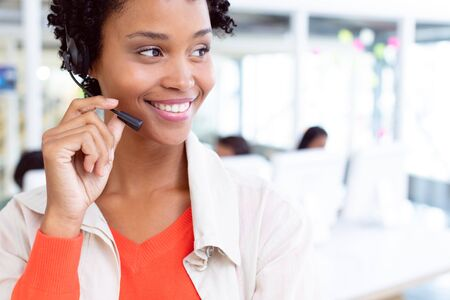 Front view of happy African-american female customer service executive standing with headset standing in office