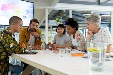 オフィスの会議室での会議で議論する多様なビジネスの人々のサイドビュー