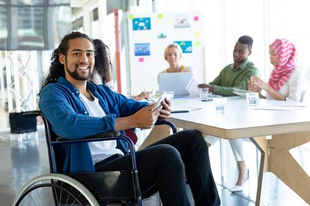 Front view of Mixed-race disabled businessman with digital tablet looking at camera in conference room during meeting in a modern office Stock Photo