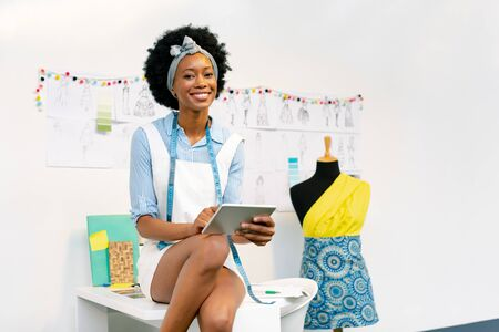 Front view of happy African american female fashion designer using digital tablet on table in office Imagens