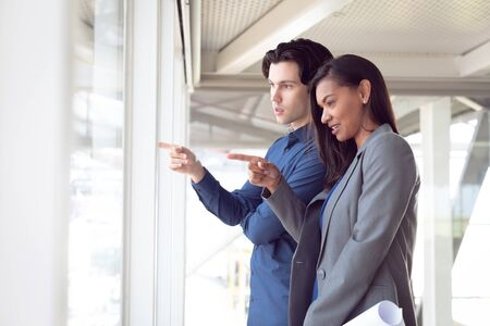 Side view of male and female architects interacting with each other in office