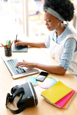 High view of African american female graphic designer using graphic tablet and laptop at desk in office Stock Photo - 124672004