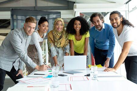 現代オフィスの会議室で一緒に働きながらカメラを見ている多様なビジネスの人々の正面図 写真素材
