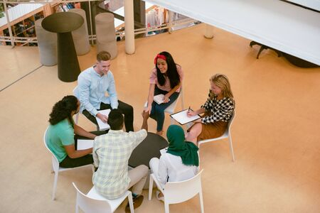 High angle view of diverse business people discussing with each other in a modern office Imagens