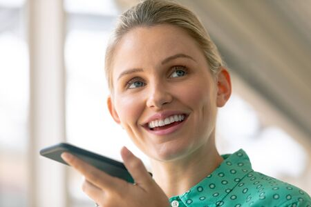 Front view of Caucasian businesswoman talking on mobile phone in office Stock Photo