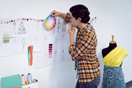 Side view of Caucasian male fashion designer looking at color swatch in office Stock Photo - 124671979