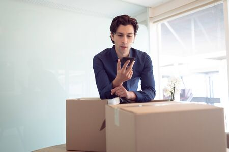 Front view of Caucasian male executive talking on mobile phone while leaning on cardboard box in office