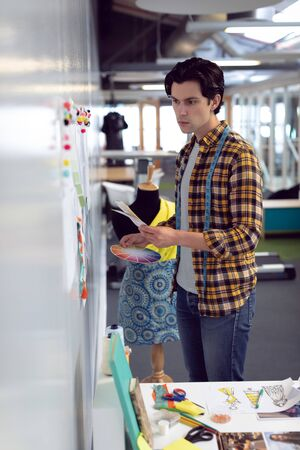 Side view of Caucasian male fashion designer looking at sketch in office Stock Photo - 124671940
