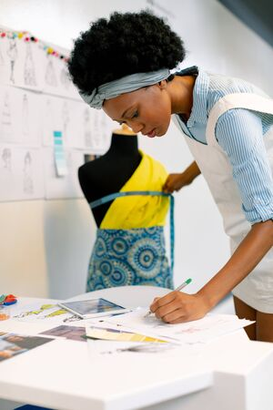 Side view of African american female graphic designer writing on paper while measuring mannequin in office Stock Photo