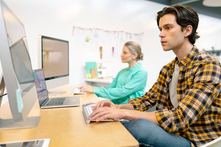 Front view of Caucasian male and female executive working on computer at desk in office Stock Photo