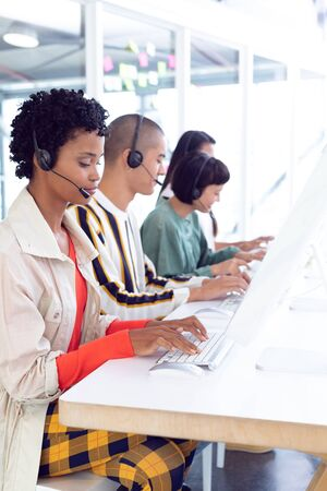 Side view of diverse customer service executives working on computer at desk in office
