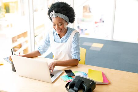 High angle view of African american female graphic designer using graphic tablet and laptop at desk in office