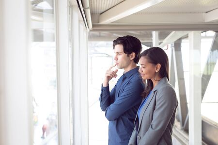 Side view of thoughtful diverse male and female architects looking through window in office