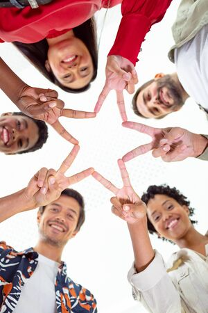 Low angle view of diverse business people forming star shape with their fingers in a modern office