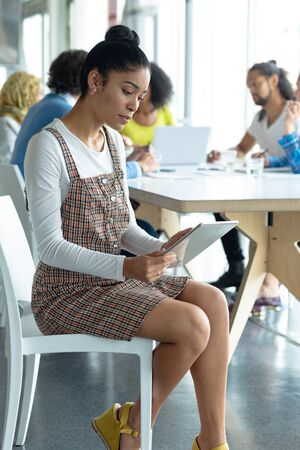 Front view of young Mixed-race businesswoman working on digital tablet in a modern office Stock Photo