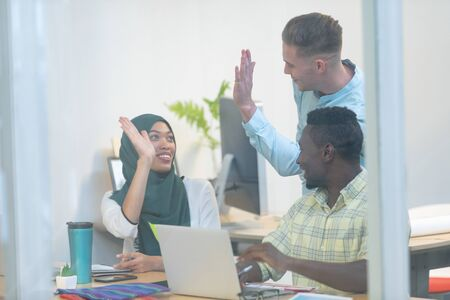 Front view of diverse business people giving high five while working together at desk in a modern office