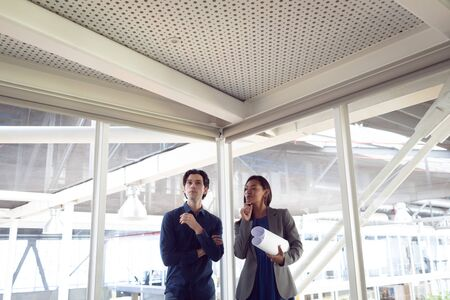 Front view of Caucasian male and female architects interacting with each other in office