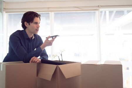 Side view of Caucasian male executive talking on mobile phone while leaning on cardboard box in office