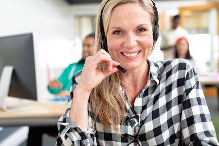 Portrait of happy Caucasian female customer service executive looking at camera while talking on headset in a modern office Stock Photo