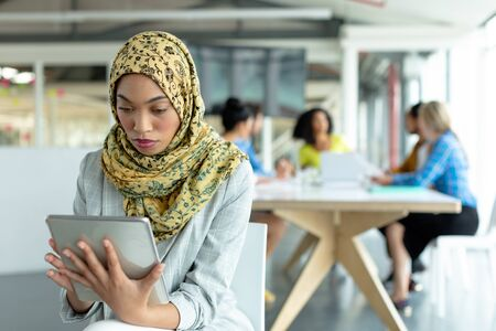 Portait of beautiful Mixed-race businesswoman in hijab working on digital tablet at conference room in a modern office
