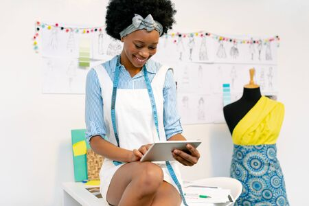 Front view of happy African american female graphic designer using digital tablet on table in office
