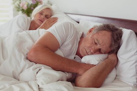 Side view of active senior Caucasian couple sleeping together in bed in bedroom at comfortable home Banco de Imagens