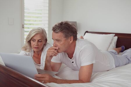 Front view of active senior Caucasian couple using laptop while lying on bed in bedroom at comfortable home